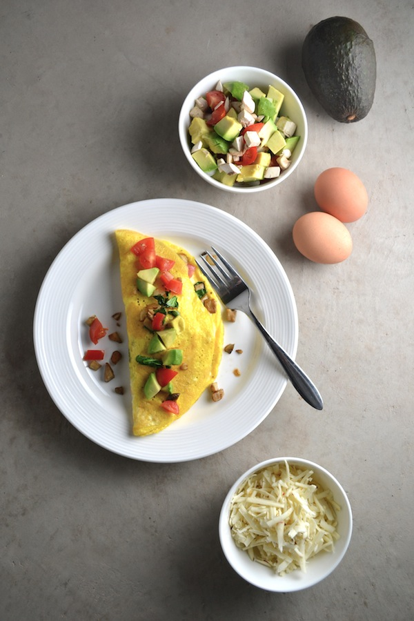 Veggie Omelet - This omelet recipe is packed with tasty vegetables like onions, mushroom, spinach, and tomatoes. Top with avocados and cheese for a quick and delicious breakfast. | twothirdscup.com