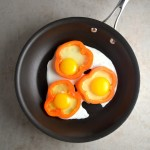 "Egg in a Pepper - This recipe is a fun twist on the traditional ""egg in a hole."" It's a really quick and healthy breakfast with fried eggs, bell peppers, and parmesan cheese. 